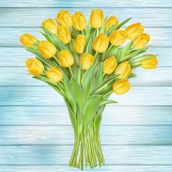 Żółci tulipany kwitną na drewnianych deskach.