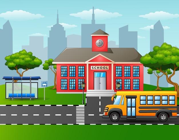 Żółty autobus szkolny przed budynkiem szkoły z przystankiem autobusowym