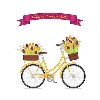 Żółty retro rower z tulipanowym bukietem w kwiecistym koszu i pudełku na bagażniku.