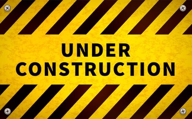Żółty znak ostrzegawczy w budowie z metalowymi śrubami w rogach