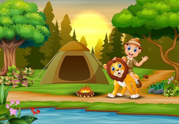Zookeeper chłopiec i lew w campingu przy zmierzchu krajobrazem