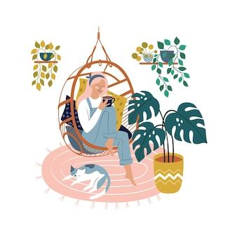 Zrelaksowana piękna kobieta siedzi w wygodnym wiszącym fotelu płaska ilustracja kobieta pije kawę w przytulnym wnętrzu domu czas dla siebie i relaks w komfortowej atmosferze