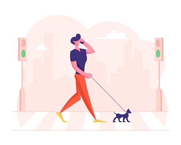 Zrelaksowany pieszy rozmawiający z psem przez smartfon idący przez przejście dla pieszych nad drogą