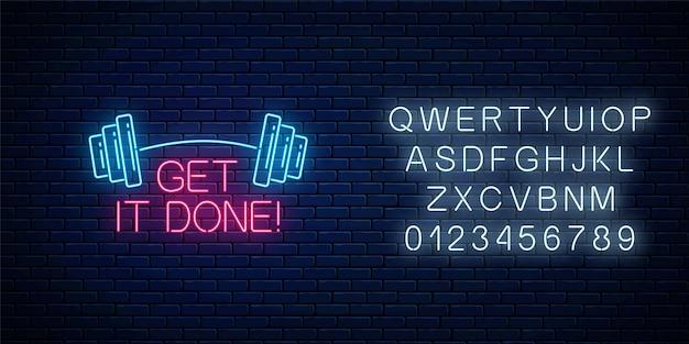 Zrób to - świecący neonowy napis ze sztangą na ciemnym tle ceglanego muru z alfabetem.