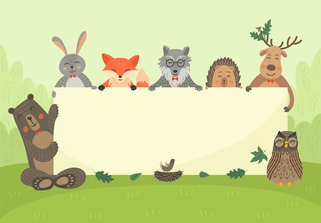 Zwierzęta leśne trzymają pusty sztandar. niedźwiedź, zając, lis, sowa, wilk, jeż i jeleń z deską. lesisty teren. ilustracja przyrody dla dzieci z miejscem na tekst.