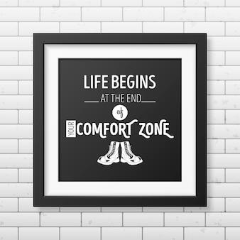 Życie zaczyna się na końcu twojej strefy komfortu - cytuj typograficzne tło w realistycznej kwadratowej czarnej ramce na tle ceglanego muru.