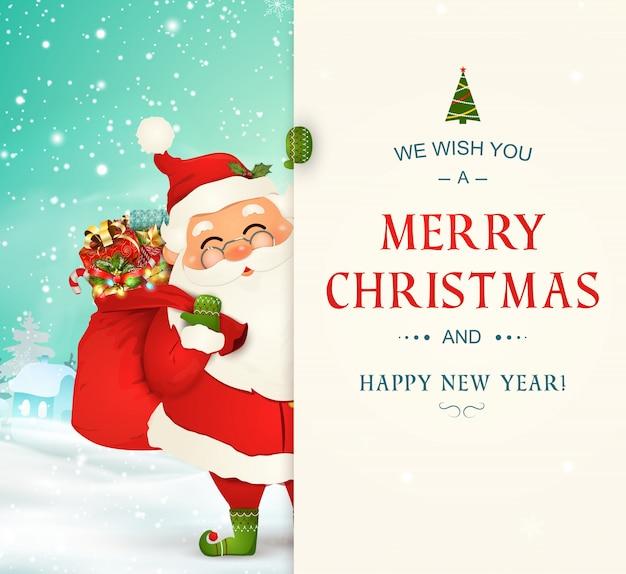 Życzymy ci wesołych świąt. szczęśliwego nowego roku. postać świętego mikołaja z dużym szyldem. święty mikołaj z torbą pełną pudełek na prezenty. kartka świąteczna ze śniegiem. na białym tle wektor.