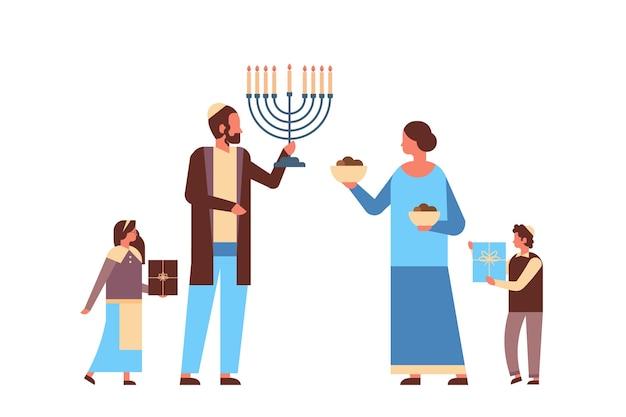 Żydowska rodzina trzymająca menorę i pudełka z prezentami żydowscy rodzice dzieci w tradycyjnych strojach stojących razem szczęśliwe święta chanuki judaizm