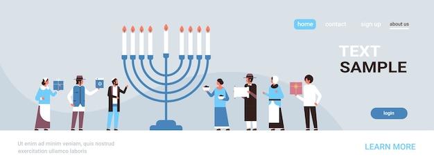 Żydzi ludzie stojący razem w pobliżu menory żydowscy mężczyźni kobiety w tradycyjnych strojach szczęśliwa chanuka