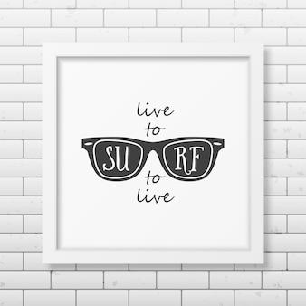 Żyj, aby surfować, surfuj, aby żyć - typograficzna realistyczna kwadratowa biała ramka na ścianie z cegły.