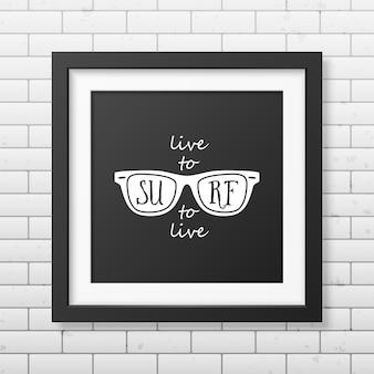 Żyj, aby surfować, surfuj, aby żyć - typograficzna realistyczna kwadratowa czarna ramka na ścianie z cegły.
