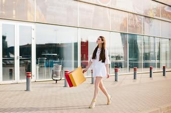 Ładna brunetka z długimi włosami spaceru z torby na zakupy przed nowoczesnym budynku ze szkła