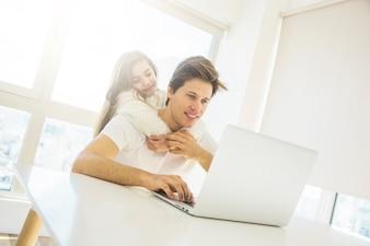 Śliczna dziewczyna ściska jej ojca używa laptop w domu