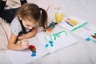 Śliczna dziewczyna maluje z jaskrawym aquarelle na podłoga