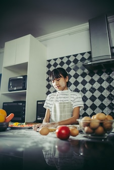 Śliczna mała dziewczynka ugniata mąki ciasta narządzanie dla robi pizzy. Gotowanie koncepcja.