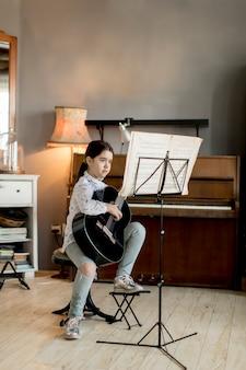 Śliczna mała dziewczynka z gitarą w pokoju