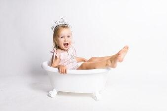 Śmieszna mała blondynki dziewczyna siedzi w skąpaniu w studiu