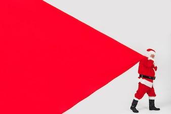 Święty Mikołaj ciągnie ogromną torbę