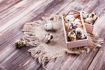 Świeże i zdrowe jedzenie, białko. Jaja przepiórcze w drewnianym pudełku stoją na stole rustykalnym