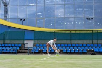 Żeński gracz w tenisa na zielonej dworskiej trawie