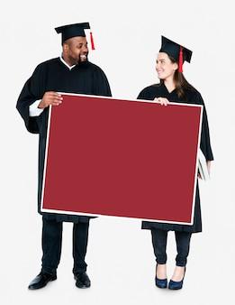Żeński i męski absolwent trzyma odbitkową przestrzeń
