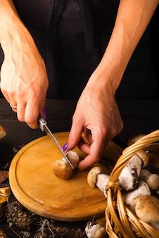 Żeńskie ręki cią świeże lasowe pieczarki na drewnianej desce