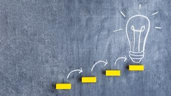 Żółty blokowy krok na żarówce rysującej na chalkboard