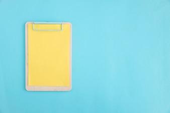 Żółty papier na drewnianym schowku nad błękitnym tłem