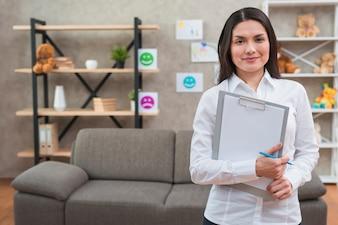 Życzliwa żeńska psycholog pozycja w jej biurze z schowkiem i ołówkiem