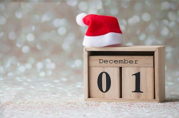 01 grudnia, pierwszy dzień zimy, drewniany kalendarz na błyszczącym tle z czerwoną czapką mikołaja