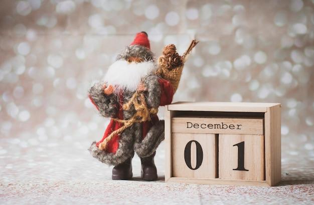 01 grudnia pierwszy dzień zimy drewniany kalendarz na błyszczącym tle ze świętym mikołajem