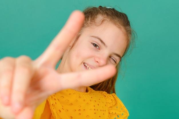 1 biała nastolatka w wieku 10 lat w żółtej bluzce mruga i pokazuje znak pokoju na zielonej powierzchni