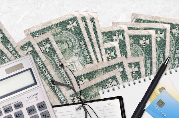 1 dolar amerykański i kalkulator z okularami i długopisem. koncepcja sezonu płatności podatku lub rozwiązania inwestycyjne.