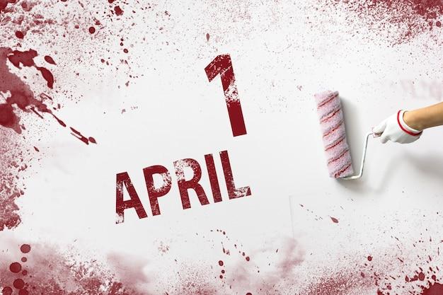 1 kwietnia. dzień 1 miesiąca, data kalendarzowa. ręka trzyma wałek z czerwoną farbą i pisze datę w kalendarzu na białym tle. miesiąc wiosny, koncepcja dnia roku.