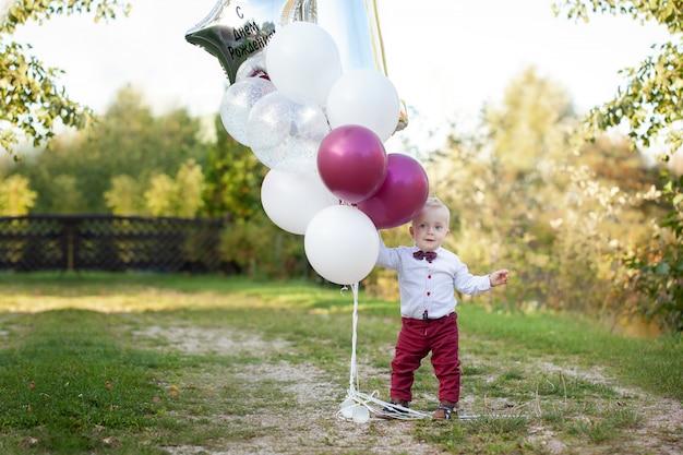 1-letni chłopiec siedzi na zielonej trawie na zewnątrz grając z balonem.