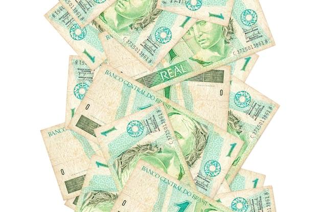 1 real brazylijski rachunki pływające w dół na białym tle. wiele banknotów spada z białymi miejscami na kopię po lewej i prawej stronie
