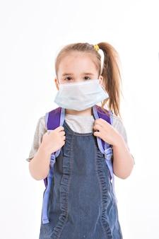 1 września. pierwsza klasa w szkole medycznej idzie do szkoły. mała dziewczynka w domu na odległość uczenia się. dziecko z plecakiem szkolnym działa. uczeń odrabia pracę domową. pojedynczo na białym tle