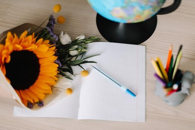 1 września powrót do koncepcji szkoły bukiet ze słonecznikiem i przybory szkolne na stole