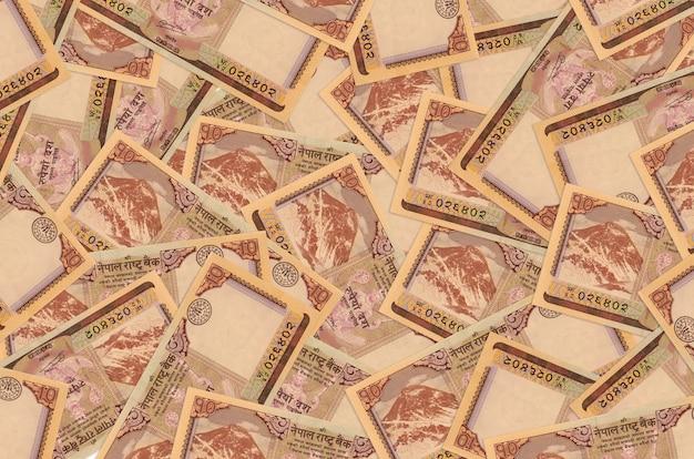 10 banknotów rupii nepalskich leży na stosie. . dużo pieniędzy