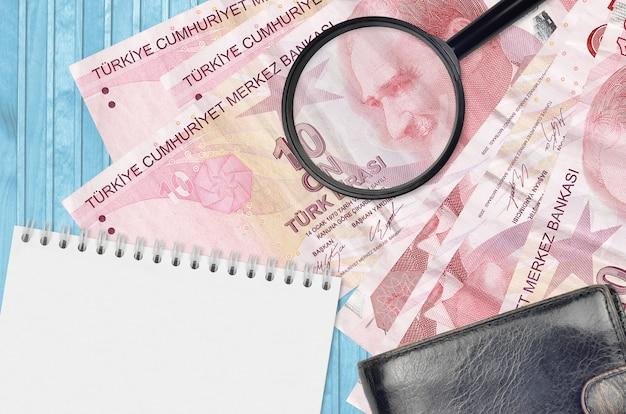 10 banknotów z lirami tureckimi, lupa, czarna torebka i notatnik. pojęcie fałszywych pieniędzy.