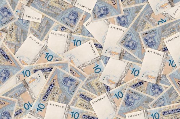 10 banknotów z tunezyjskich dinarów leży na stosie. ściana koncepcyjna bogatego życia. duża suma pieniędzy