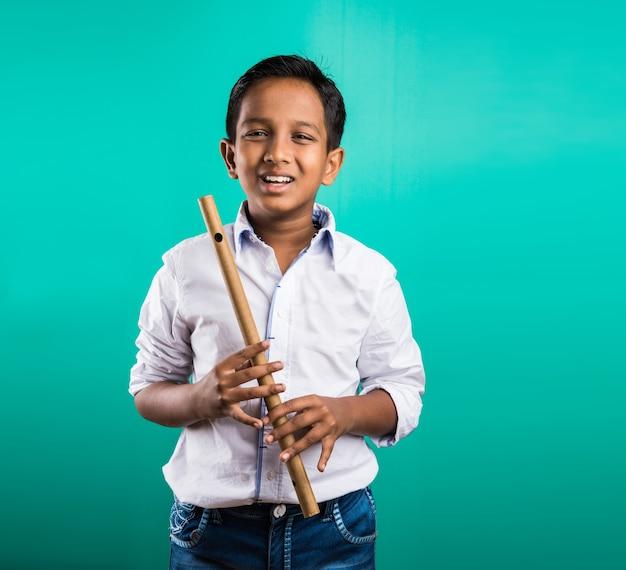 10-letni indyjski ładny chłopiec grający na flecie lub instrumencie muzycznym, odizolowany na zielonym tle