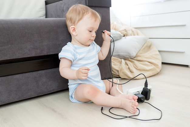 10-miesięczny chłopiec ciągnący kable z przedłużacza elektrycznego