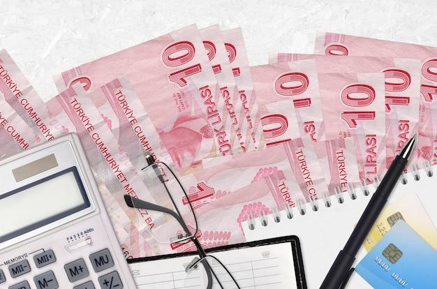 10 rachunków lir tureckich i kalkulator z okularami i długopisem. koncepcja sezonu płatności podatku lub rozwiązania inwestycyjne.
