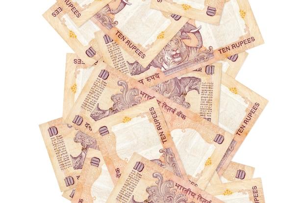 10 rachunków rupii indyjskich lecących w dół na białym tle. wiele banknotów spada z białą przestrzenią na kopię po lewej i prawej stronie