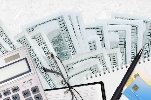 100 dolarów rachunków i kalkulator z okularami i długopisem. koncepcja sezonu płatności podatku lub rozwiązania inwestycyjne. planowanie finansowe lub dokumenty księgowe