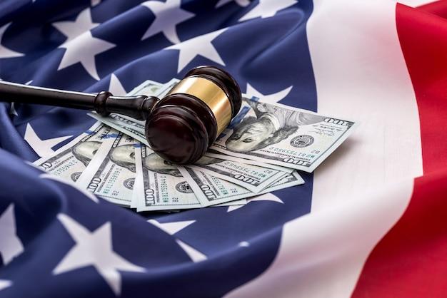 100-dolarowe banknoty i młot sędziowski na amerykańskiej fladze.