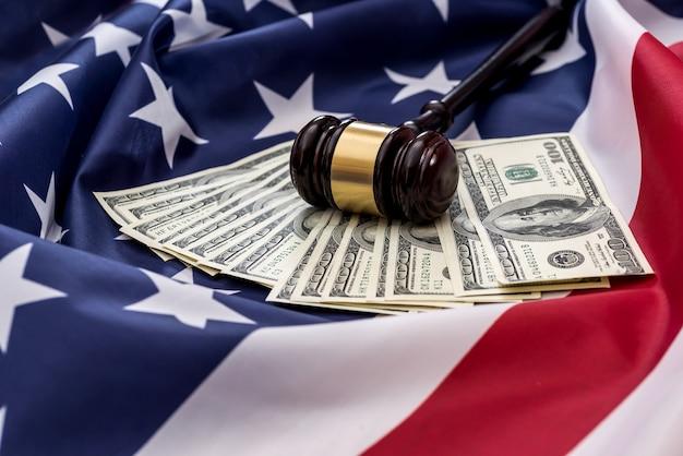 100-dolarowe banknoty i młot sędziowski umieszczone na amerykańskiej fladze
