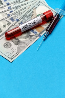 100 rachunków dolarowych i próbki krwi w probówce na niebieskim tle.
