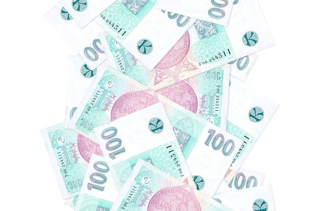 100 rachunków koron czeskich pływające w dół na białym tle. wiele banknotów spada z białymi miejscami na kopię po lewej i prawej stronie